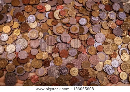 lots of coins lying around leather wallet on the table