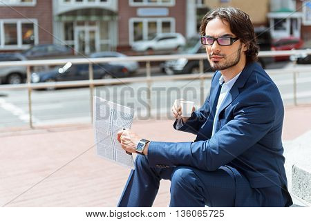 Smart young man is having rest outdoors. He is sitting and drinking coffee. Worker is holding a newspaper and looking forward pensively