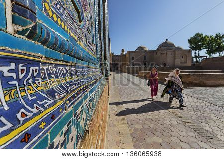 SAMARKAND, UZBEKISTAN - MAY 19, 2016: Women walk in the holy cemetry of Shakhi  Zinda in Samarkand, Uzbekistan.