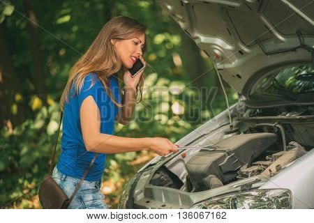 Beautiful young worried woman standing by car that broke down on the road in forest holding wrench and talking at mobile phone.