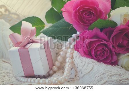 fresh pink roses with lace, pearls and gift box, retro toned