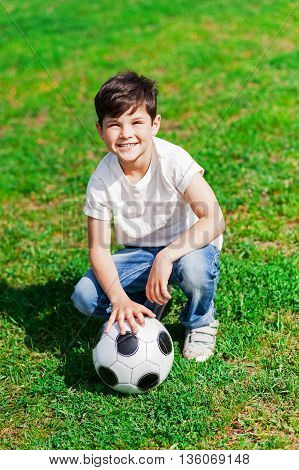 Pretty male child is sitting on grass and touching a football ball. He is looking at camera with happiness and smiling