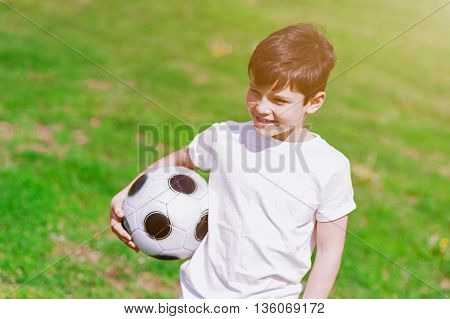 Cute small boy is holding a football ball. He is standing on grass and smiling