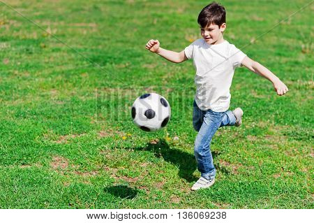Skillful small football player is ready to kick the ball. He is running and stretching his leg. The boy is smiling happily