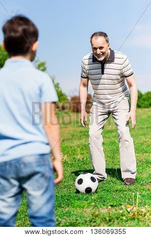 Cheerful grandfather and his grandchild are playing football in park. The man is preparing to kick the ball and smiling. The boy is standing and waiting