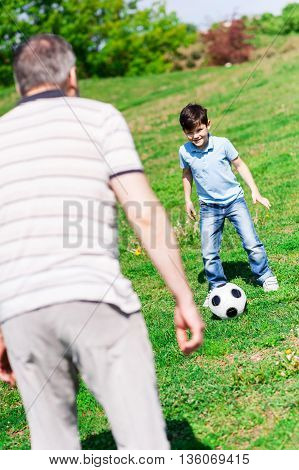 Cute family is playing football together. They are standing on grass. Small boy is preparing to kick the ball to his grandfather and smiling