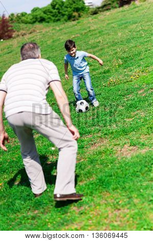 Happy boy and his grandfather are playing football in park. The child is kicking the ball and smiling