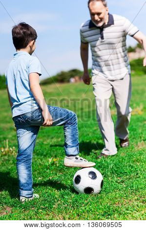 Cheerful old man is playing football with his grandson. He is running to a ball and smiling. The boy is standing on grass and leaning leg on toy