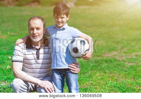 Portrait of friendly grandfather and his grandson resting in park together. They are embracing and looking at camera with happiness. Boy is holding a ball and smiling. Copy space in right side