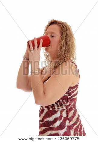 A image of a blond woman in a summer dress standing in profile drinking from a red coffee mug isolated for white background.