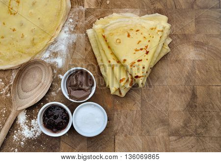 homemade french pancakes with accompaniments in bowls on wooden plank