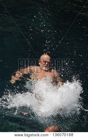 A swimmer splashing and kicking his feet in the sea