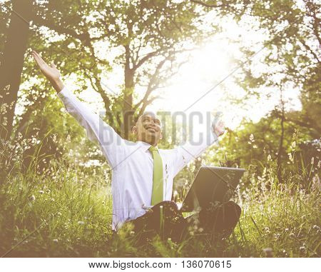 Businessman sitting in a forest with his laptop.