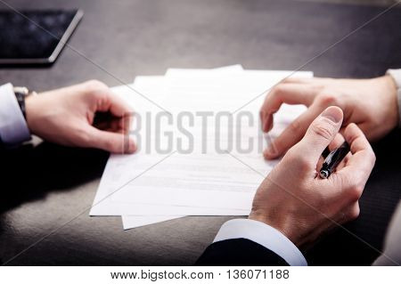 Closeup of male hand pointing where to sign a contract, legal papers or application form