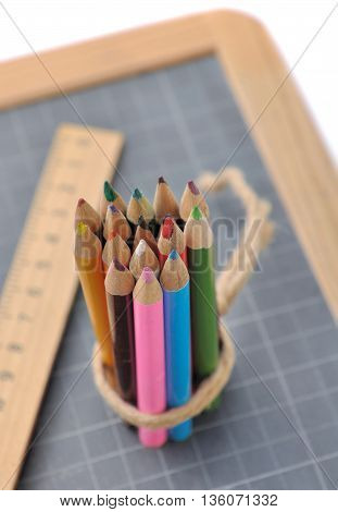 package of colored pencils with wooden rule on a slate