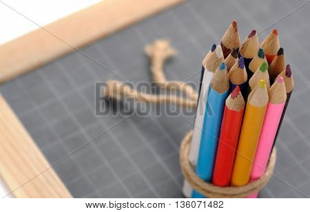 colored pencils tied by string  on a slate