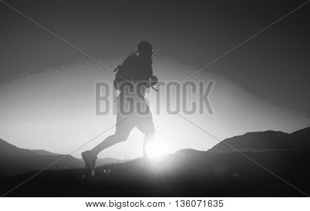 Man's Silhouette Running In A Sunset With Mountain Concept