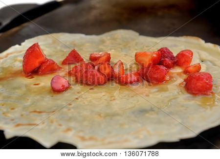 preparing a french pancake with strawberries and honey