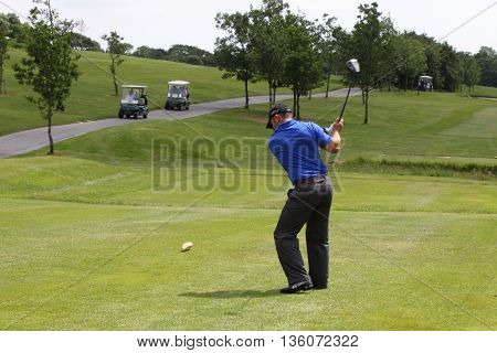 7TH JUNE 2016, OKEHAMPTON, ENGLAND: A golfer driving his golf ball down the fairway on a golf course in Okehampton, England, june 2016