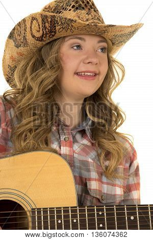 A close up of a cowgirl with down syndrome playing her guitar with a smile.