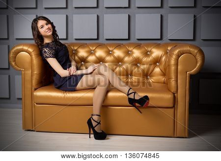 Young girl in black dress on sofa