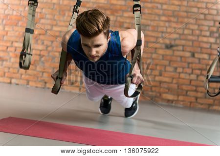 Cheerful young man is doing push-ups with concentration. He is holding trx equipmwent