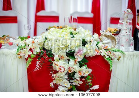 Decoration wedding feast with red ribbons and white flowers