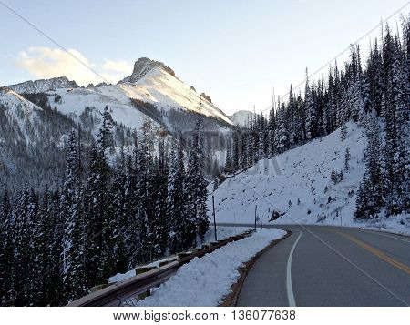 Road winding through snow covered mountains and forests