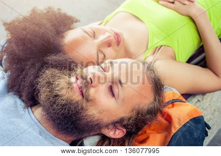 Closeup of beautiful backpacker tourist napping on a bench