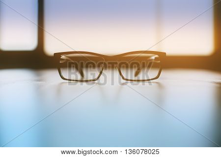 Backlit spectacles on bright desktop with window in the background