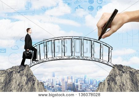 Success concept with hand drawing bridge over gap between two cliffs and businessman walking across it on city background with business sketches