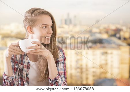 Pretty caucasian girl drinking coffee on sunlit blurry city background