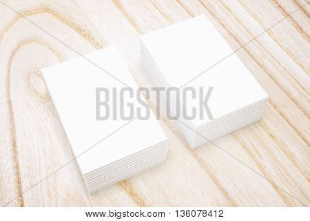 Two stacks of blank business cards on natural wooden surface. Mock up 3D Rendering