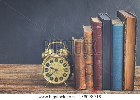 row of old books with antique alarm clock on wooden shelf, retro toned