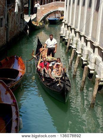 Venice,  Italy - June 10 2006: Tourists riding taking a gondola ride along a narrow canal poled by a Venetian boatman