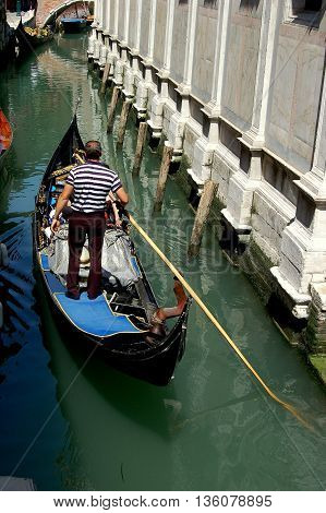 Venice, Italy - June 10 2006: Gondolier steers his black gondola with a long wooden pole along a small Venetian canal