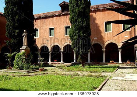 Venice Italy - June 10 2006: Tranquil cloister with cypress trees at San Francesca della Vigna church