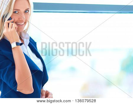 Businesswoman standing against office window talking on mobile phone .