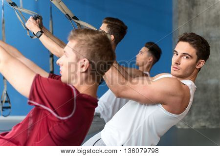 Handsome fit man is training with group in gym. He is leaning hands on trx equipment. Athlete is looking at camera with confidence