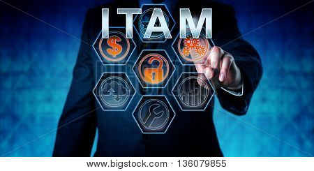 Business person is touching ITAM on an interactive virtual control monitor. Business strategic metaphor information technology concept corporate terminology and acronym for IT Asset Management.