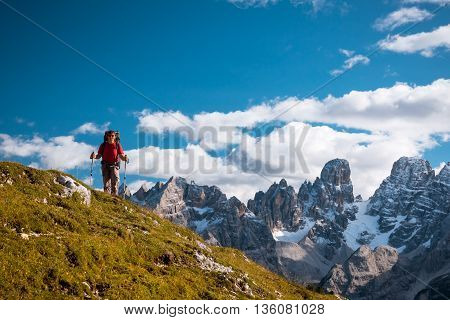 Female hiker with backpack standing on path in Dolomite mountains