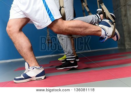 Close up of young men training legs with trx trap. They are standing in gym