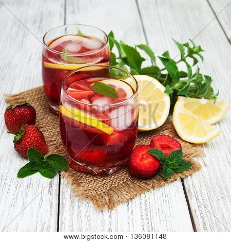 Glasses of lemonade with strawberries on the table