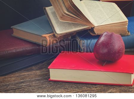 Pile of books with apple on wooden bookshelf, retro toned
