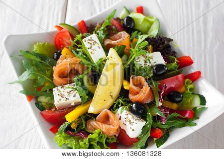 Mediterranean salad with salmon and brie top view. Appetizing salad with salmon, brie, olives and vegetables, served with lemon slice in white bowl on wooden table.