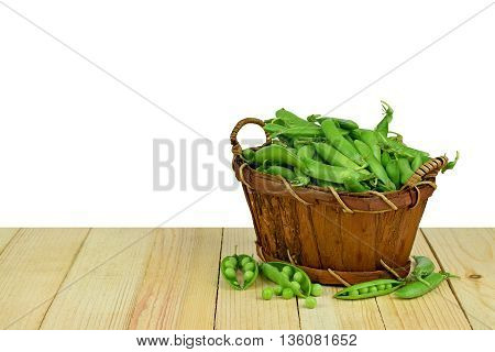Fresh pods of green peas in the basket on wooden background. / Isolation on a white background /. Summer. Vitamins. Rustic style. Natural health products.