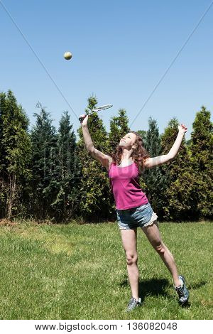 Girl with racket and ball on backyard in the summer