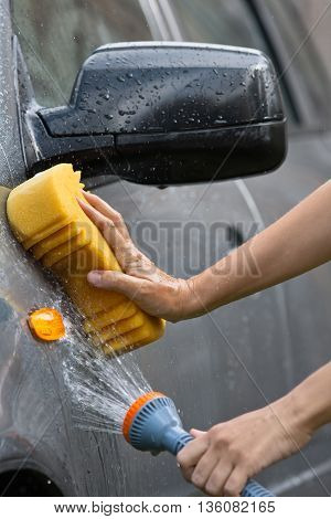 hand washing grey car with flowing water and sponge closeup