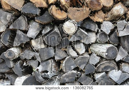 A large old pile of weathered fire wood.
