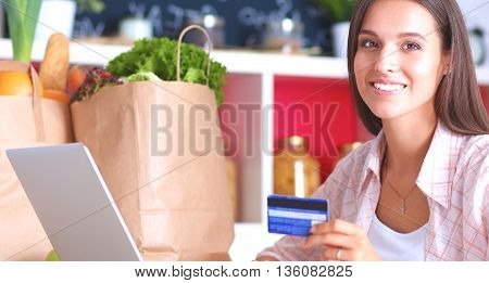 Smiling woman online shopping using tablet and credit card in kitchen.